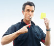 Soccer referee blowing whistle and pointing at a yellow card