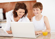 Happy mother assisting her son while using laptop at home