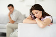 Relationship problem - Worried young couple sitting separately o
