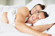 Young couple lying on bed and smiling