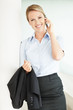Smiling confident young female executive using a cell phone