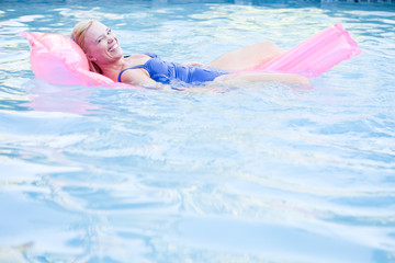 Woman floating on airbed in swimming pool