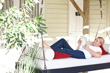 Mature woman holding tablet computer in hanging lounger on veranda