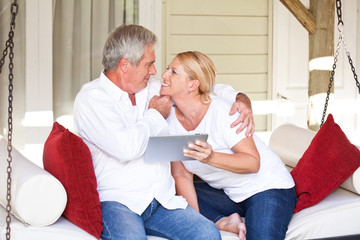 Mature couple with tablet computer in hanging lounger on veranda