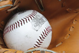 Close up of baseball in catcher's mittt with shallow depth of fi