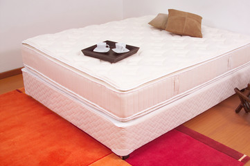 Unmade bed with breakfast tray
