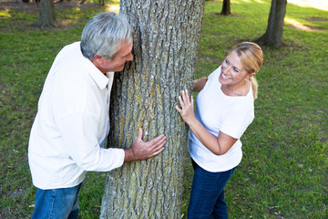 Smiling mature couple standing at tree