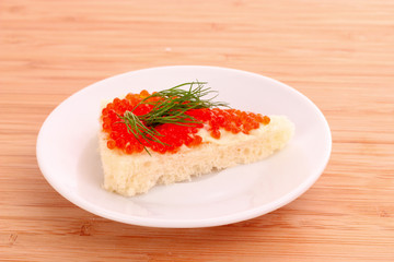 Red caviar and bread on wooden table