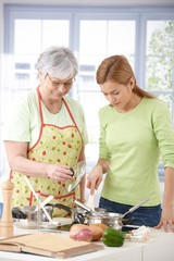 Senior mother and daughter cooking together