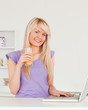 Beautiful female drinking orange juice and relaxing on a laptop