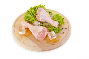 Fresh and frozen chicken legs on chopping board