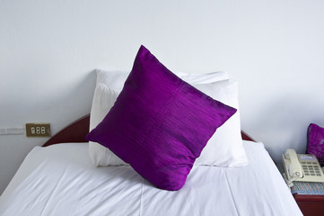 Hotel bedroom interior with  purple pillows.