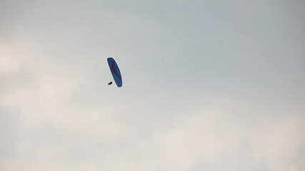 Paraglider glide and down against the sky
