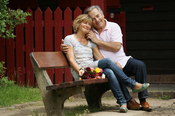Glückliches älteres Paar sitzt auf einer Bank
