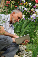 homme senior se servant d'une tablette tactile