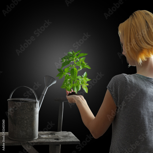 Gardening concept - woman holding a plant