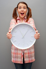 scared woman showing wall clock