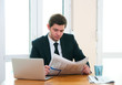 Young businessman having breakfast and reading newspaper