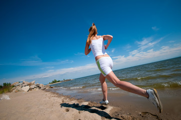 Sport woman running on beach