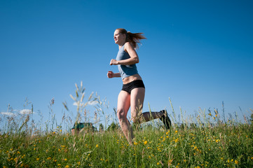 Sport woman running over green grass and sky
