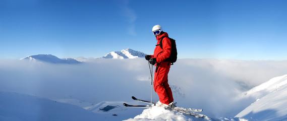 Skifahrer steht am Gipfel