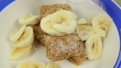 Sugar being sprinkled on to Weet Bix with banana.