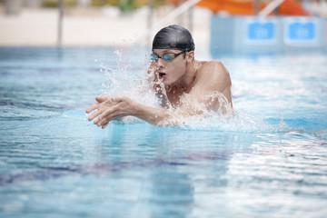 Swimmer in cap breathing performing the breaststroke
