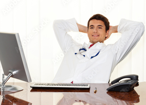 Successful physician sits at a desk