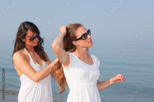 Young Woman Dress Her Friend's Hairs at Seaside