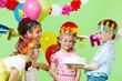 Preschool boy offering birthday cake to his guests