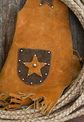 Western theme rope leather vest on old wood shelf
