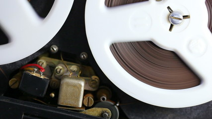 Open reel audio tape recorder reels spinning.Close-up.