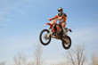 Motocross rider on the motorbike takes off his head turned