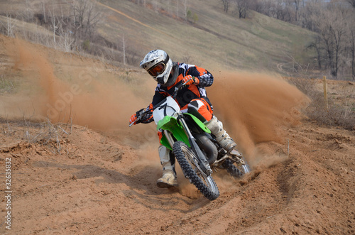 Motocross rider with a strong slope turns sharply - 32635832