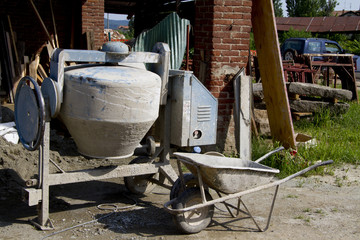 details of a construction site with wheelbarrows and cement mixe