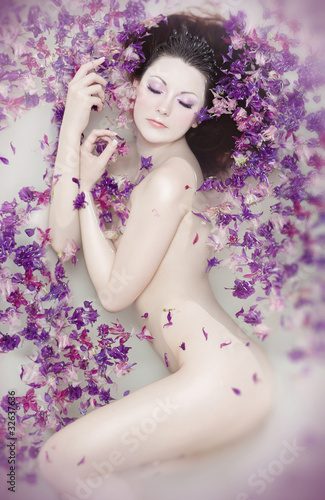 Attractive naked girl enjoys a bath with milk and rose petals.