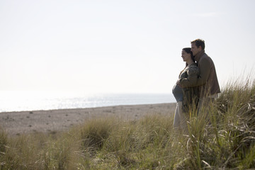 A pregnant woman and her partner standing, looking out to sea