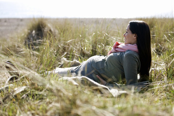 A pregnant woman lying amongst long grass, looking out to sea