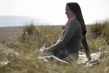 A pregnant woman sitting amongst the sand dunes, smiling