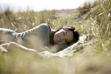 A pregnant woman lying amongst long grass, smiling