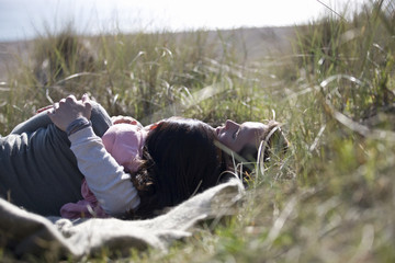 A pregnant woman and her partner sleeping in amongst long grass