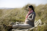 A pregnant woman sitting amongst the sand dunes