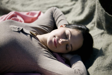 A young woman sleeping on a blanket, outdoors