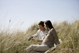 A pregnant woman and her partner sitting amongst the sand dunes