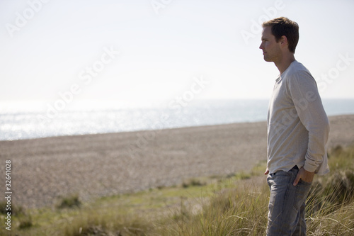 A young man standing amongst the sand dunes, looking out to sea