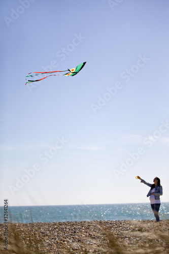A pregnant woman flying a kite on the beach