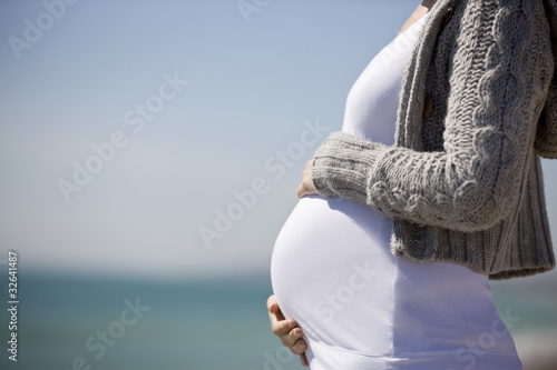 A pregnant woman standing on the beach, holding her belly