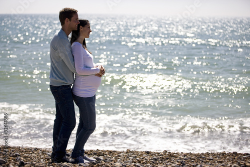A pregnant woman and her partner embracing on the beach