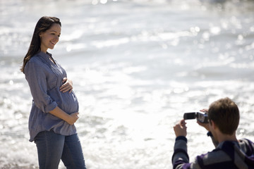 A young man filming his pregnant partner on the beach