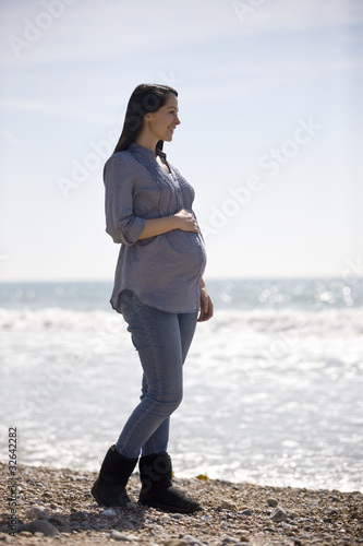 A pregnant woman standing on the beach, smiling
